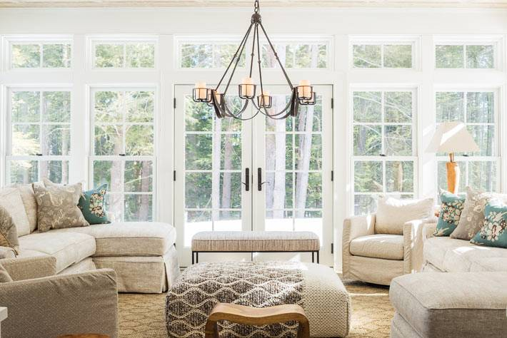 светлое пространство гостиной комнаты со стеклянной стеной