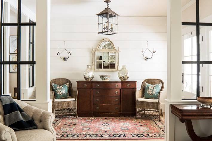 старинный комод и плетёные кресла в комнате с красным ковром