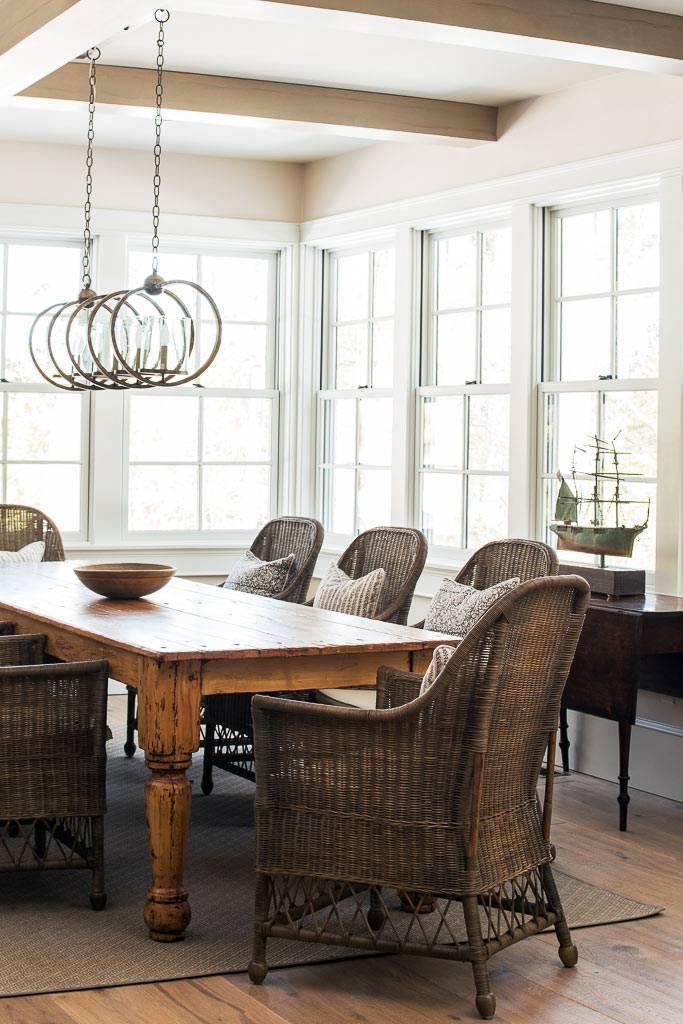 массивный деревянный стол и плетёные кресла в обеденной зоне