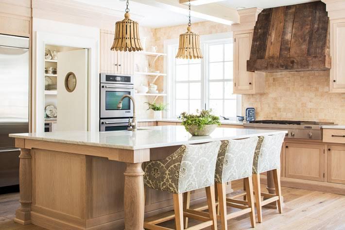 кухня с большим островом и барными стульями в доме