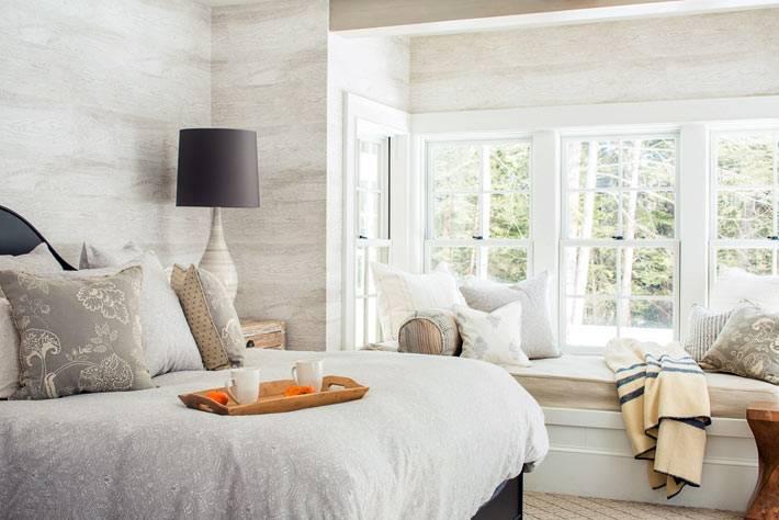 мягкий подоконник с подушками и пледом в интерьере спальни