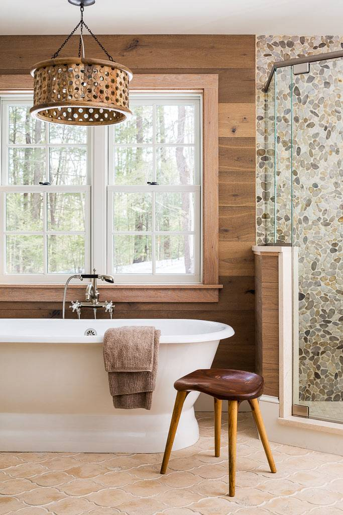 чаша ванны перед большим окном в ванной комнате