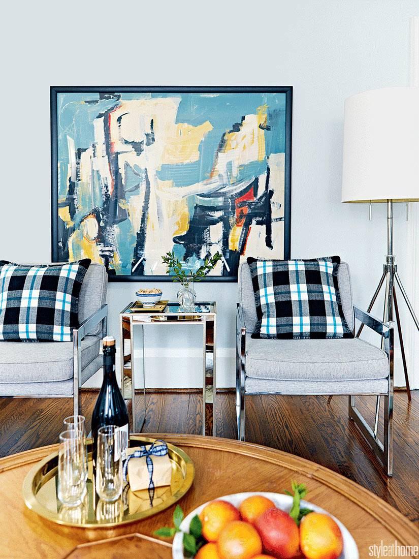 декоративные подушки из клетчатой ткани на серых креслах в комнате
