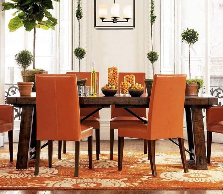 изысканная столовая с высокими оранжевыми мягкими стульями