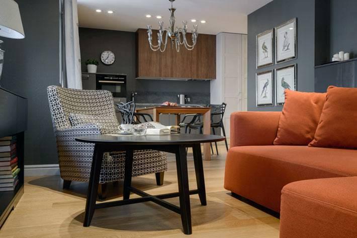 яркий оранжевый диван на фоне темно-серых стен в доме
