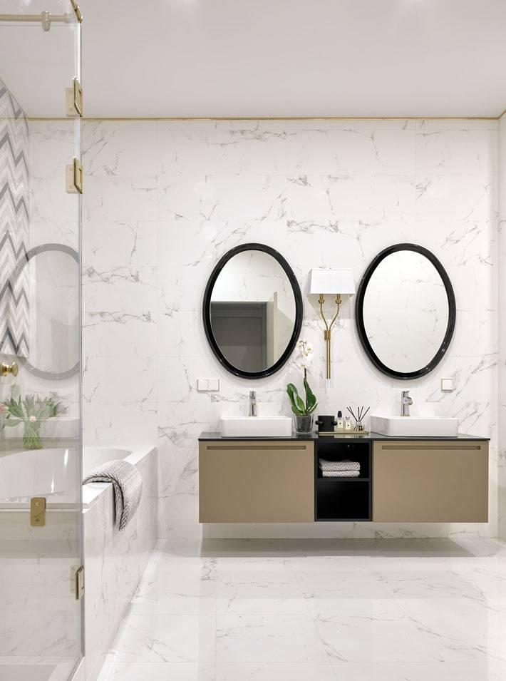 овальные зеркала в черных рамах над раковинами в ванной комнате