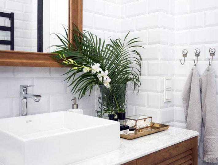 зеленый цветок папоротника освежает белый интерьер ванной комнаты