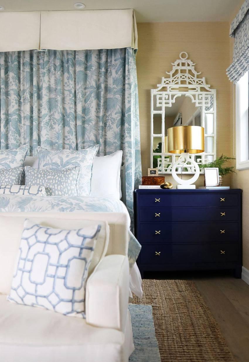 красивый интерьер спальни с песочным цветом стен и синими комодами