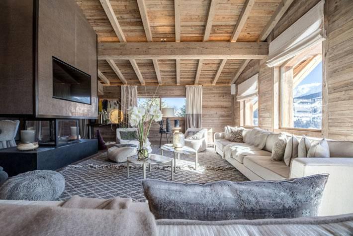 деревянный интерьер гостиной комнаты с камином и балками на потолке