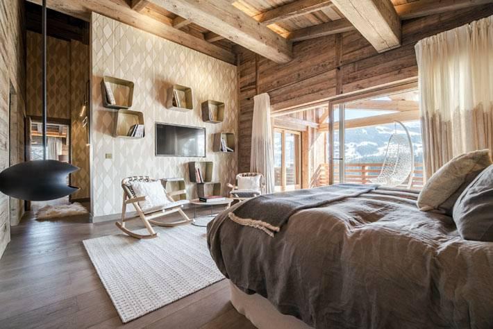 большая спальня с деревянными стенами и камином