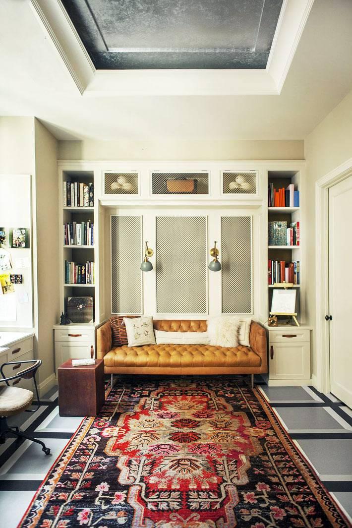 рыжий диван на ножках в нише из белого шкафа