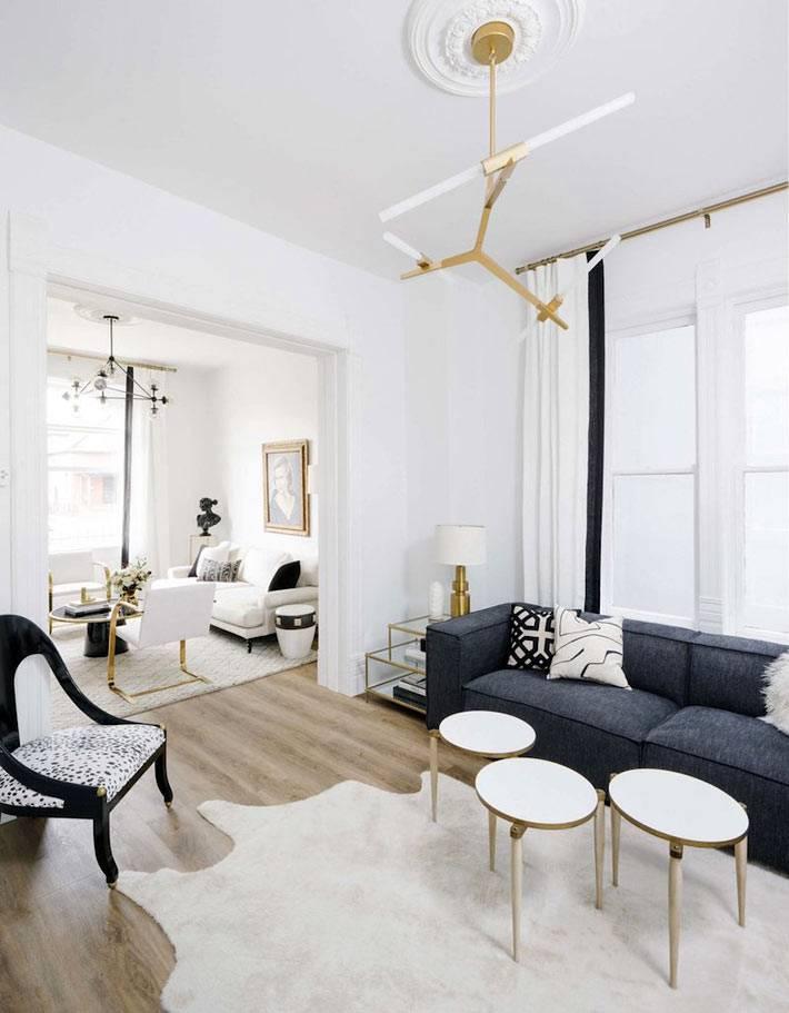 белая шкура на полу комнаты и темно серый диван фото