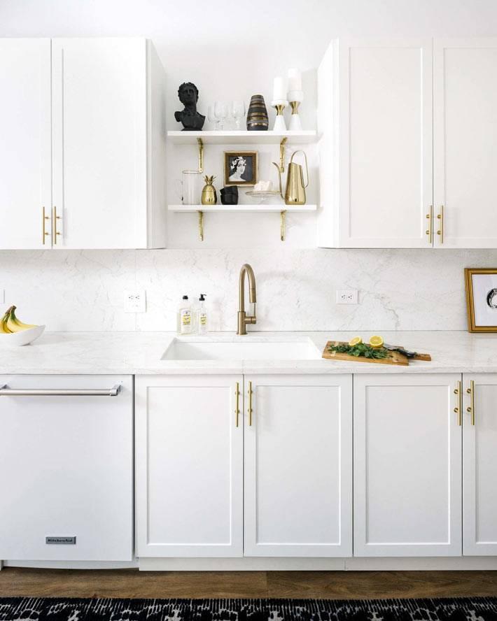 белая кухонная мебель с латунными ручками и открытыми полками