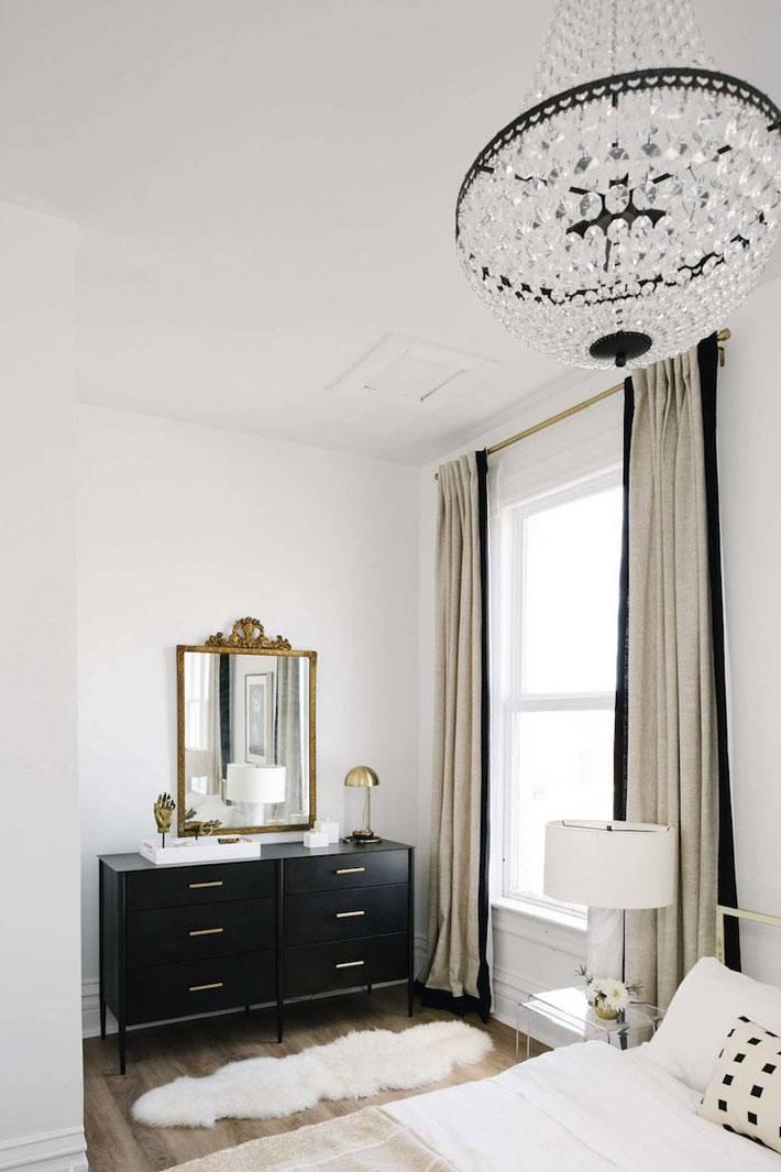 черный комод на ножках и зеркало в золотой раме в спальне