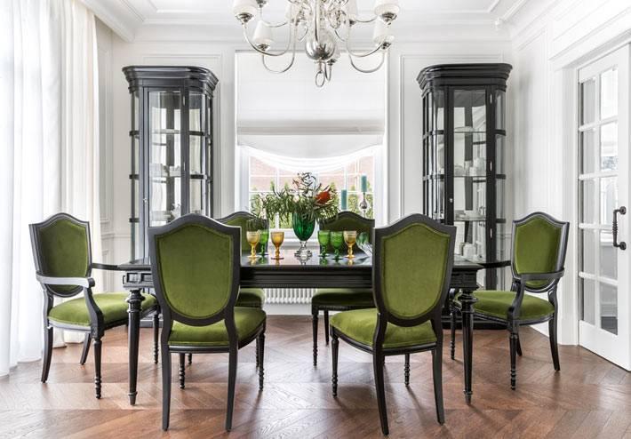 красивый столовый зал в доме для приема гостей с зелеными стульями