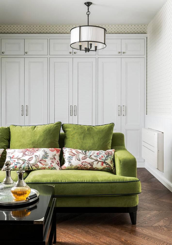бархатный диван зеленого цвета в комнате отдыха