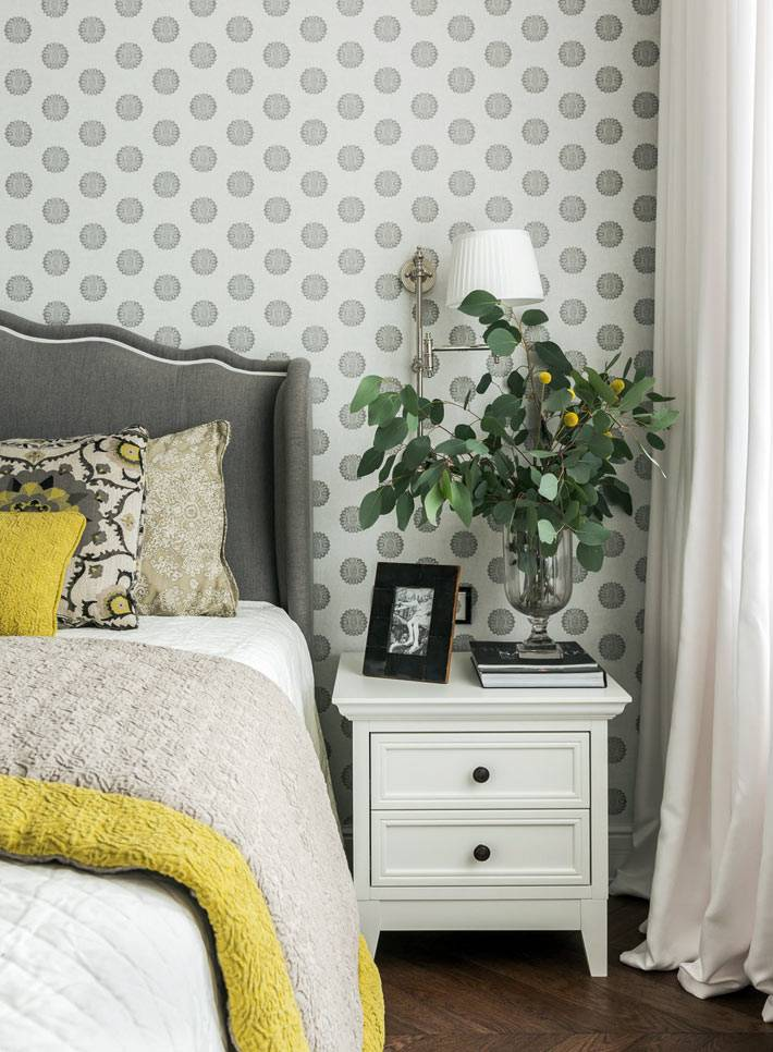 высокое серое изголовье кровати гармонирует с серыми обоями
