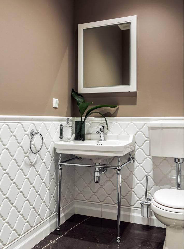 стены туалетной комнаты оббиты белыми панелями и коричневыми обоями