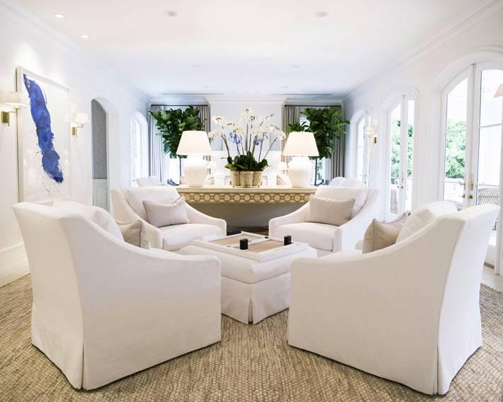 зона комфортного отдыха состоит из белых кресел и оттоманки