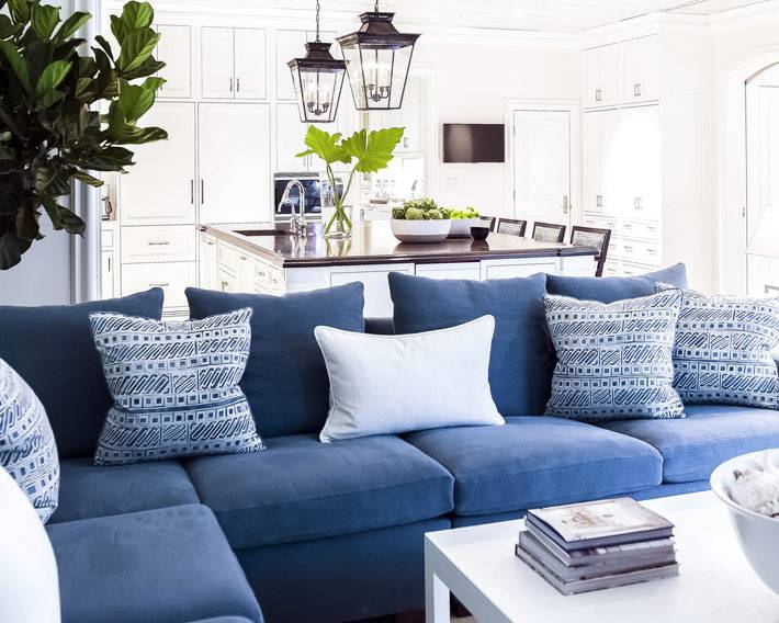 мягкий синий диван с подашками установлен в зоне отдыха на кухне
