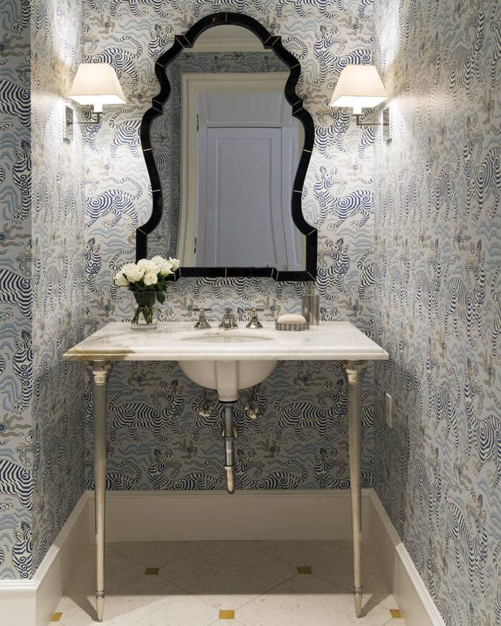фигурное зеркало в черной раме украшает стену ванной комнаты