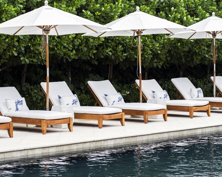 лежаки с белыми матрасами у бассейна загородного дома