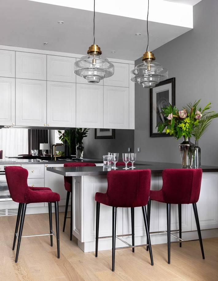 яркие красные стулья оживили белый интерьер кухни