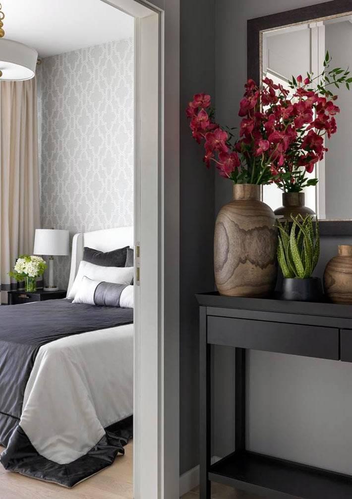 перед входом в спальню стоит черная консоль с зеркалом и цветами