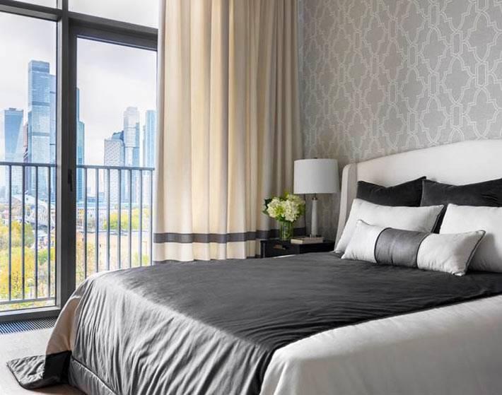 спальня с панорамным окном выполнена в серой гамме