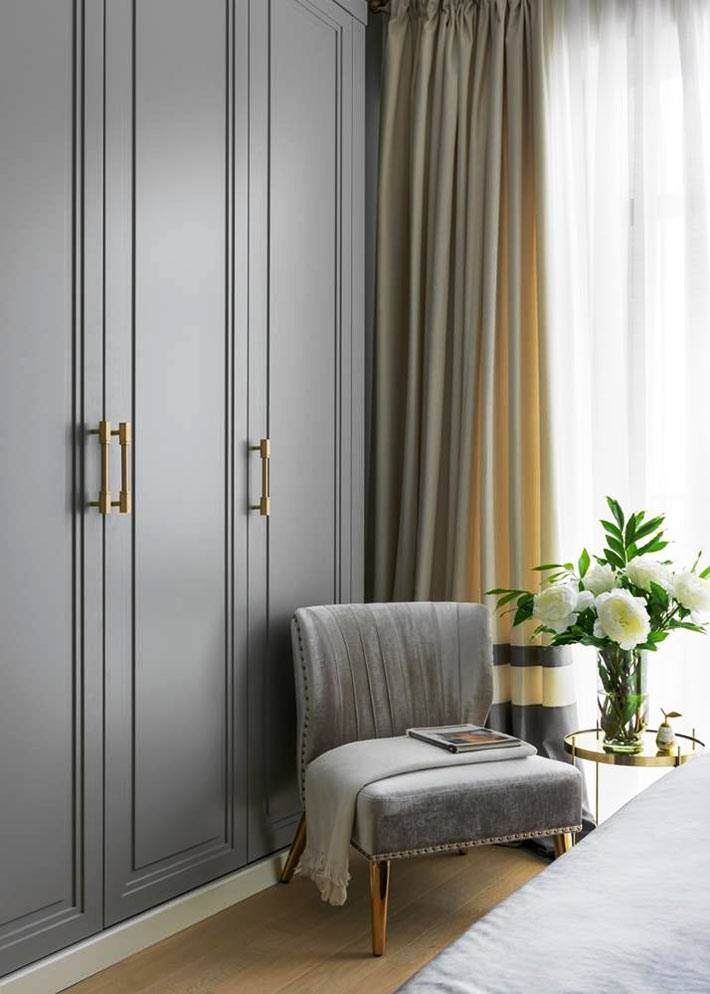 напротив кровати установлен большой серый шкаф для одежды