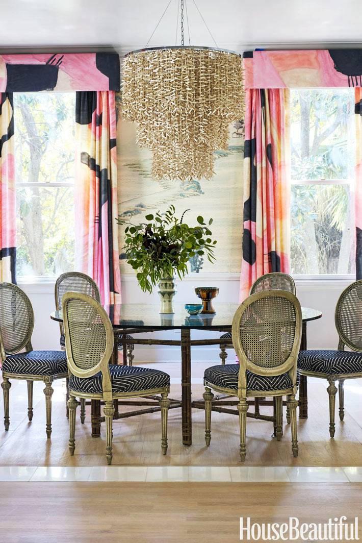 пестрые шторы с радужным розово-черным рисунком в столовой комнате