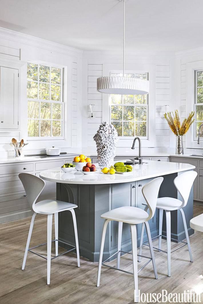 эргономичная кухня белого цвета с овальным столом-островом