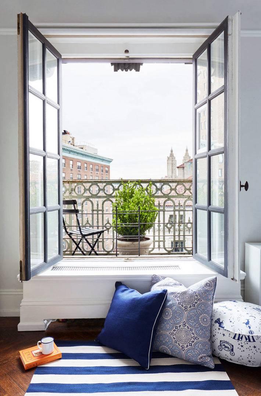 яркие напольные подушки возле открытого окна с видом на город