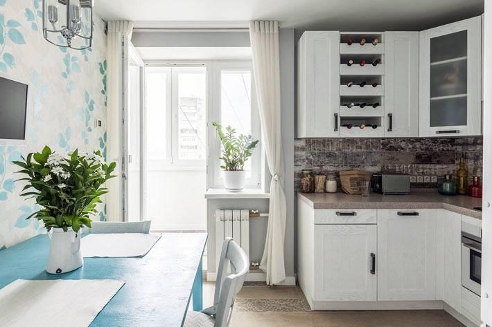 уютная кухня с белой мебелью и синим обеденным столом