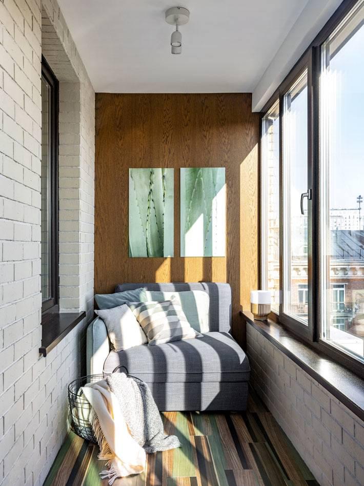 уютное кресло с подушками на закрытом балконе-лоджии