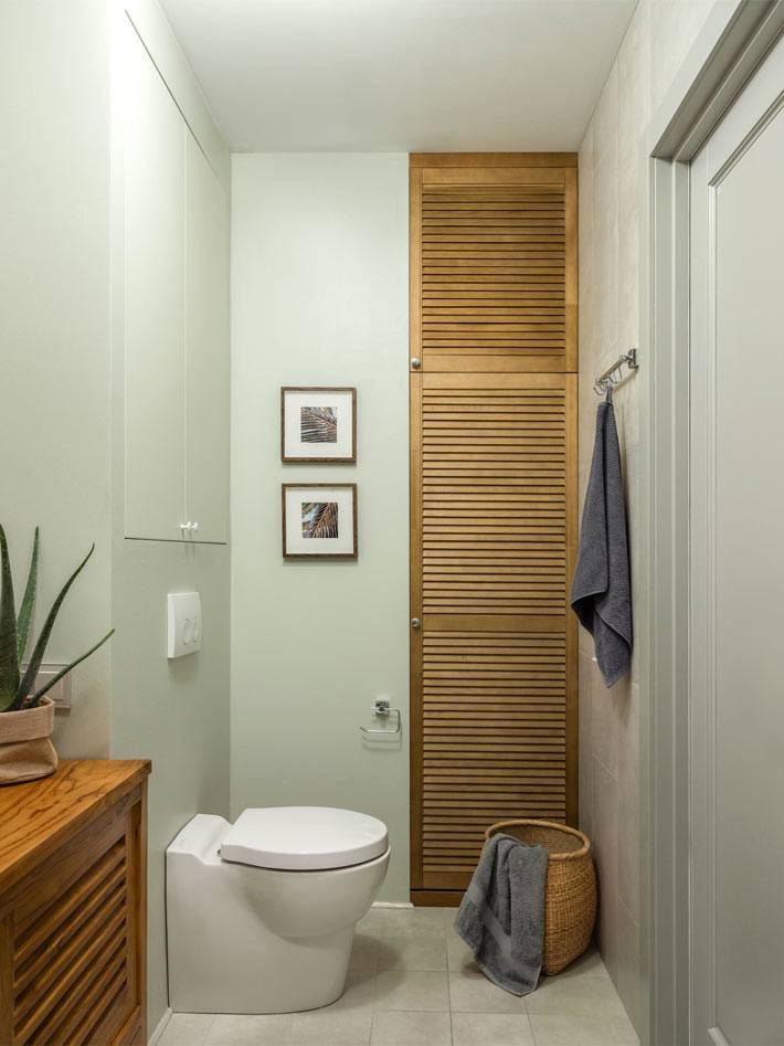 встроенный шкаф в нише туалета с деревянными дверцами