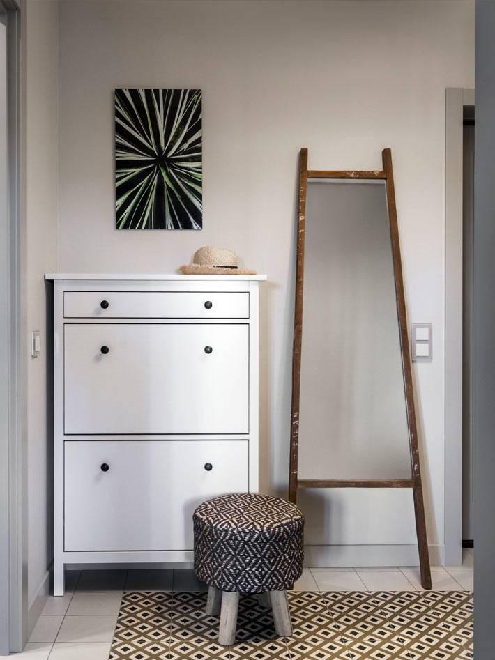 оригинальное зеркало в прихожей и белая галошница