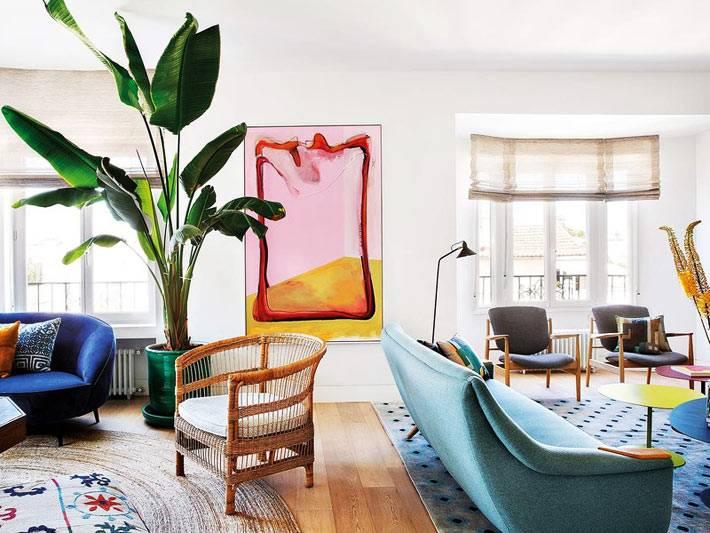 синие диваны и ротанговое кресло рядом с большим комнатным растением
