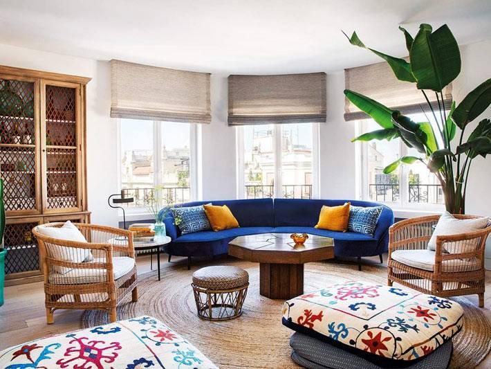 полукруглый синий диван с оранжевыми подушками