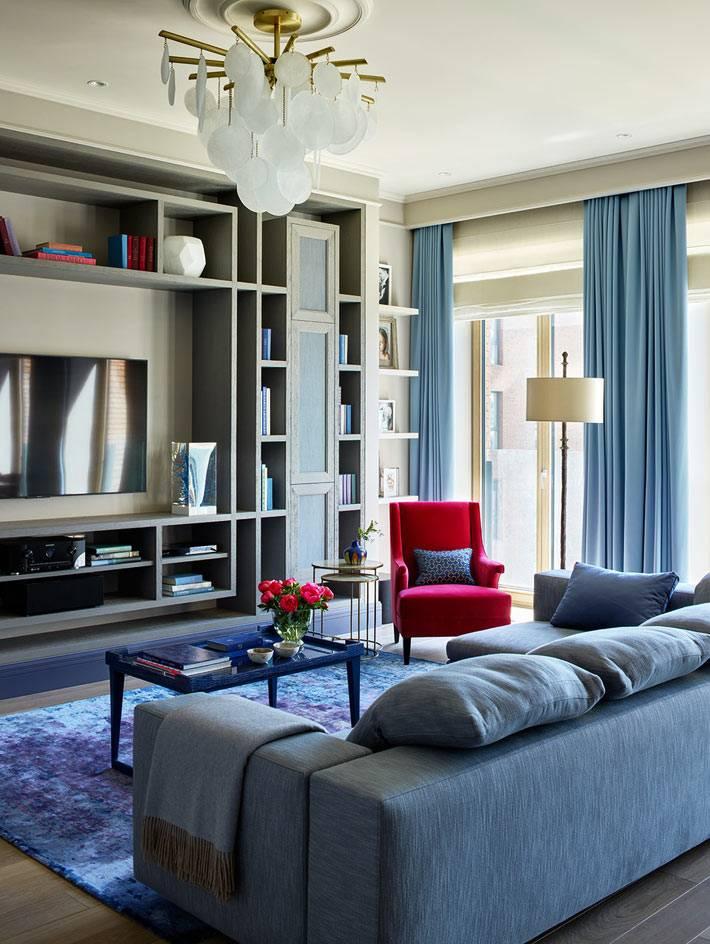 голубые шторы в комнате сочетаются с голубым диваном и ковром