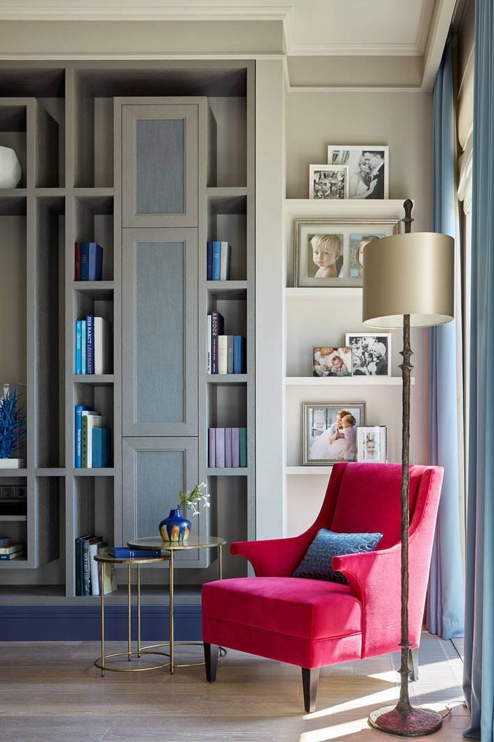 стеллажный шкаф в гостиной и розовое кресло под торшером