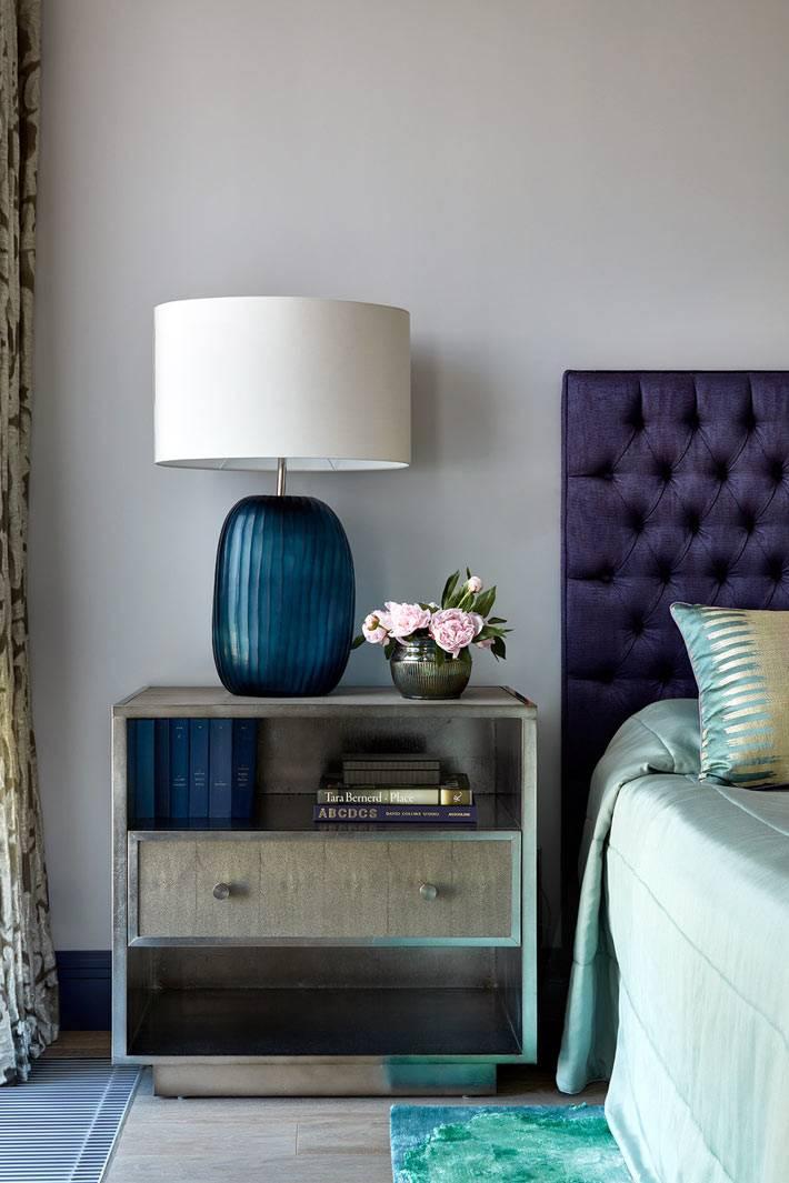 синяя настольная лампа на металической прикроватной тумбочке