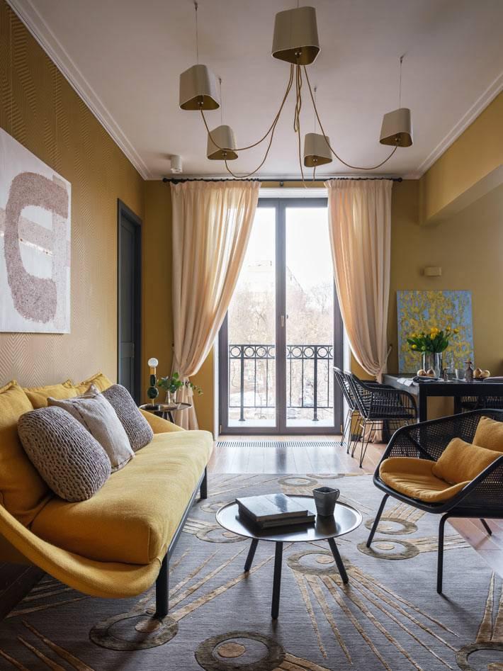 гостиная комната с желтыми обоями и желтой мягкой мебелью