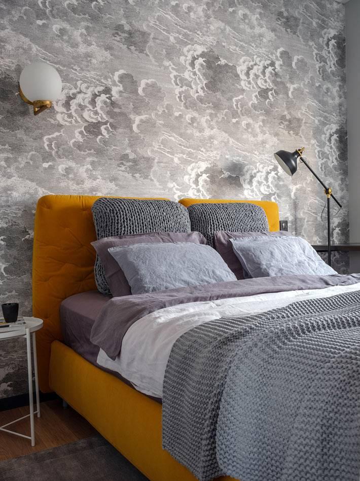серые обои с облаками на акцентной стене за кроватью в спальне
