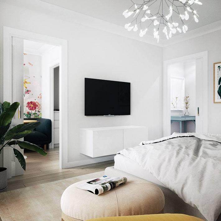 телевизор и подвесная тумба напротив кровати в спальне