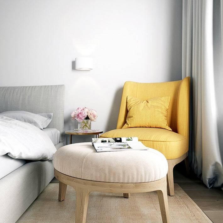 круглый пуфик-оттоманка и мягкое желтое кресло в квартире