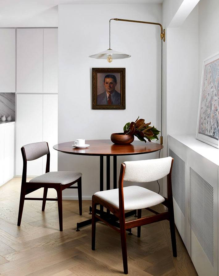 круглый столик из темного дерева дополнен двумя белыми стульями
