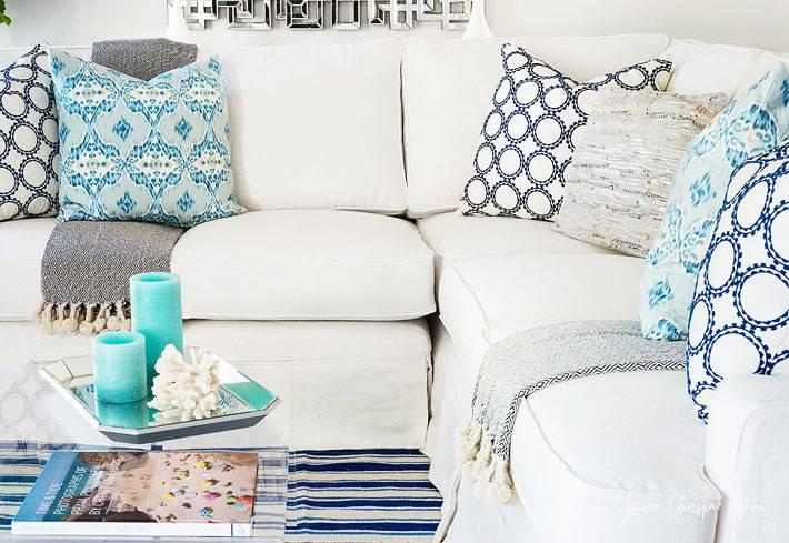 белый диван в гостиной с разными подушками фото