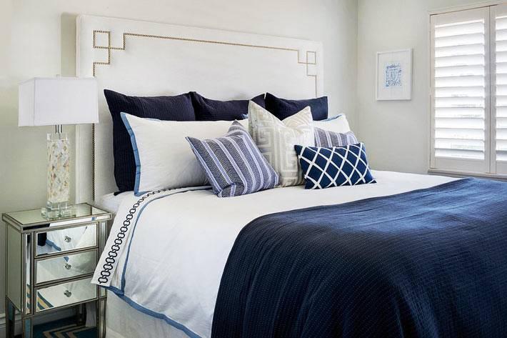 кровать с высоким белым изголовьем и зеркальные тумбы в спальне