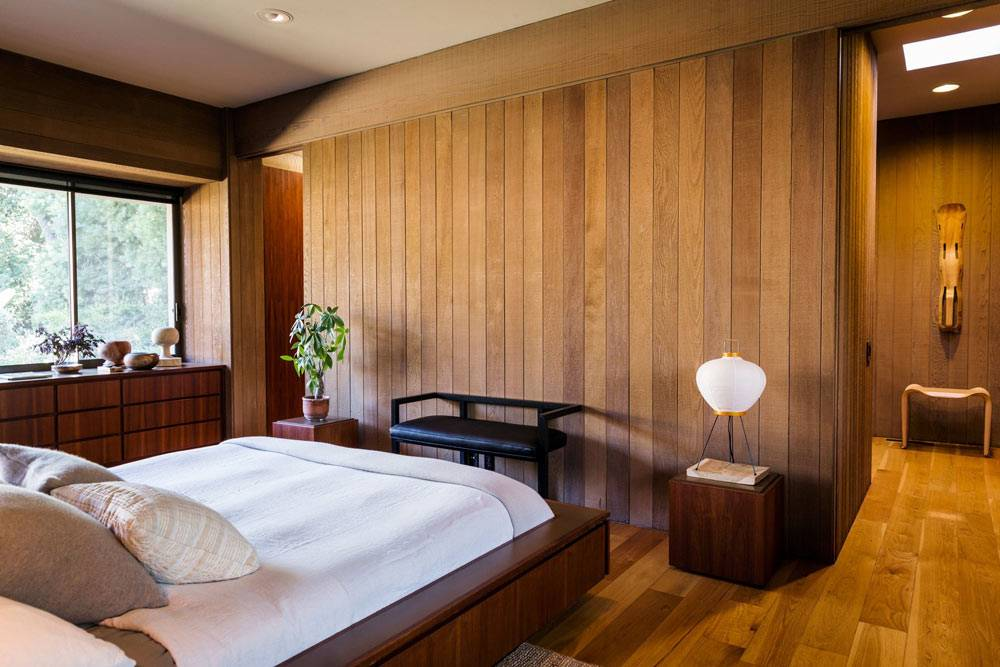 лаконичная спальня с деревянными стенами и тумбой под окном
